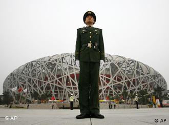 A police officer guards the Bird's Nest prior to the opening ceremony outside the National Stadium during Beijing Olympics in Beijing, Friday, Aug. 8, 2008.(AP Photo/Charlie Riedel)