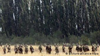 Georgian soldiers marching through a field in front of a forest