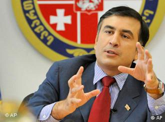 Georgian President Mikheil Saakashvili gestures in front of a Georgian coat of arms