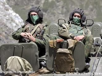 Two Russian solders with their faces covered sit on a tank