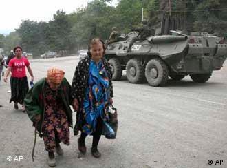Women walk near a tank