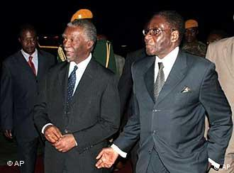 South African President Thabo Mbeki, left, is accompanied by Zimbabwean President Robert Mugabe, center, on Mbeki's arrival for talks in Harare Saturday, Aug. 9. 2008. Mbeki came to the country to mediate talks between Mugabe's party and the opposition. (AP Photo)