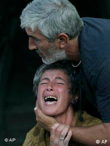 An unidentified crying Georgian woman is calmed by her husband in the town of Gori, Georgia
