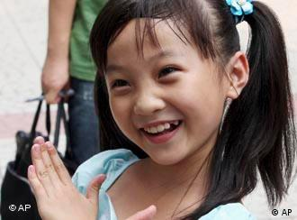In this photo released by China's Xinhua News Agency, Lin Miaoke, a nine-year-old Chinese girl who performed at the opening ceremony of the Beijing Olympics on the day before, returns to the Xizhongjie Primary School of Dongcheng District in Beijing on Saturday, Aug. 9, 2008. A 7-year-old Chinese girl's face was not suitable for the Olympics opening ceremony, so Lin lip-synched Ode to the Motherland, the latest example of the lengths Beijing took for a perfect start to the Summer Games. (AP Photo/Xinhua, Zhou Liang)