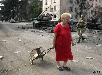 A woman is seen with a cart of her belongings, in a street in Tskhinvali, capital of Georgian breakaway enclave of South Ossetia