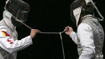 China's Zhu Jun, left, and Germany's Benjamin Philip Kleibrink get tangled during the men's individual foil semifinals at the Beijing 2008 Summer Olympics in Beijing, Wednesday, Aug. 13, 2008. (AP Photo/Domenico Stinellis)