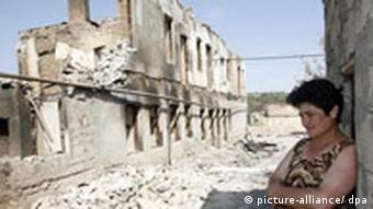 A Sotuh Ossetian woman stands amid ruins in the destroyed city of Tskhinvali