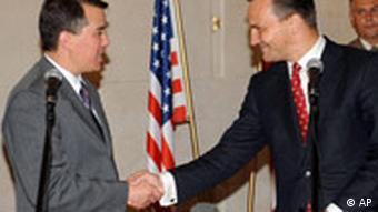 Polish Foreign Minister Sikorski shakes hands with chief US negotiator John Rood after an initial agreement on conditions for placing a US missile defense base in Poland was signed