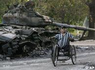Ein  verwundeter Mann im Rollstuhl vor einem zerstörten Panzer (Foto: AP)