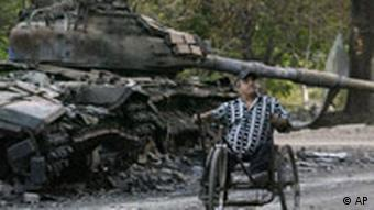 A man in a wheelchair passes a destroyed tank in South Ossetia