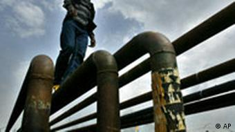 An unidentified man walk on oil pipelines near an oil flow station belonging to Agip Oil company in Obrikom, Nigeria, Monday, March 6, 2006. Armed militants in Nigeria vowed Sunday to cut daily oil exports from this West African nation's troubled delta region by another 1 million barrels by the end of March, as OPEC nations prepared for a strategy meeting in Vienna this week. A wave of militant assaults on pipelines and oil facilities has already cut production by 455,000 barrels per day in Nigeria, which normally exports 2.5 million barrels of crude daily. (AP Photo/George Osodi)