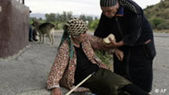 A displaced Georgian woman is helped up on the outskirts of Gori, northwest of the capital Tbilisi