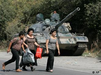 Georgian refugees walk past a Russian tank in the village of Igoeti, 50 kilometers (31 miles) from Tbilisi, Georgia
