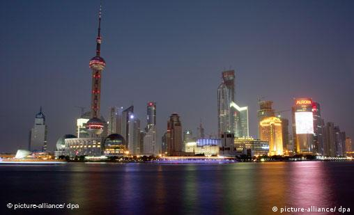 The Shanghai skyline with bulbous TV tower on the waterfront is illuminated after sunset