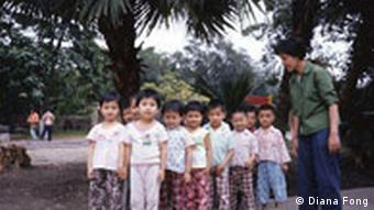 Group of small Chinese children with their teacher in a park