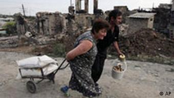 Residents walk past destroyed buildings in Tskhinvali, in the Georgian breakaway province of South Ossetia