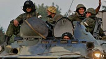Russische Soldaten sitzen bewaffnet mit Sturmgewehren auf einem gepanzerten Fahrzeug an der abchasischen Grenze zu Georgien