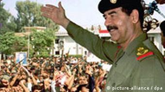 Iraks Präsident Saddam Hussein winkt jubelnden Menschen in Bagdad zu (Foto: dpa)