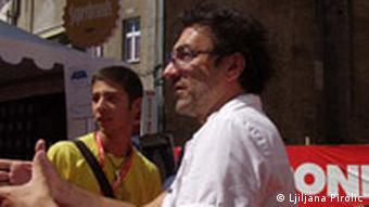 Poznati režiser Branko Đurić na SFF-u. Razgovara sa nekim od uposlenihz na SFF-u. U bijeloj košulji i sa naočalama.