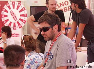Bosanskohercegovački režiser, Srđan Vuletić na jednoj od projekcija SFF-a. U plavoj košulji, sa naočalama. Oko njega ljudi razgovaraju.