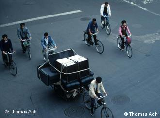 Years ago, several Chinese riding bikes on city street, where there are no vehicles. One Chinese guy transports a huge sofa on his bike.