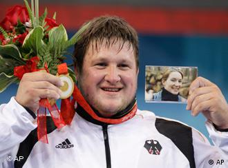 Matthias Steiner of Germany holds the gold medal he's dedicating to his late wife Susann