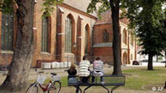 Jugendliche auf einer Bank vor dem Seitenflügel einer Kirche (16.6.07, Wittstock, Quelle: AP)