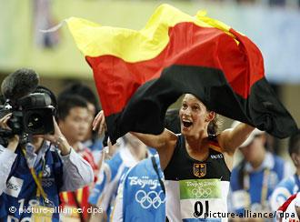 Lena Schoeneborn carries a German flag after winning the modern pentathlon.