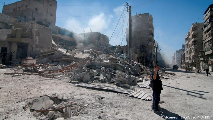 A man gestures after an airstrike struck a building in Aleppo
