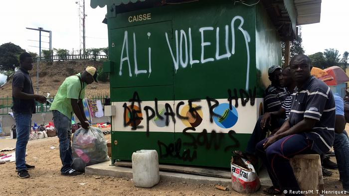 People stand next to graffiti which reads 'Ali Thief' in French