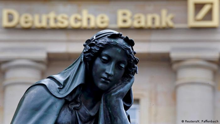 A statue is seen next to the logo of Germany's Deutsche Bank