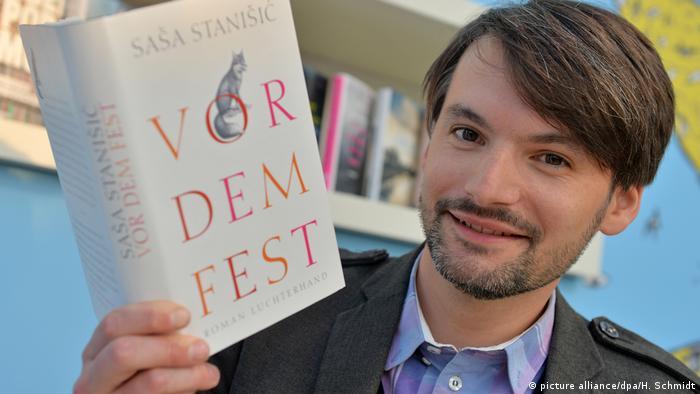 Sasa Stanisic hält lächelnd sein Buch Vor dem Fest in die Kamera (picture alliance/dpa/H. Schmidt)