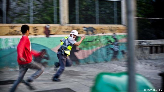 Policial militar de São Paulo é perseguido por manifestante após ficar isolado de sua tropa em um protesto em setembro de 2013, durante enfrentamento que deixou ao menos uma pessoa ferida gravemente.