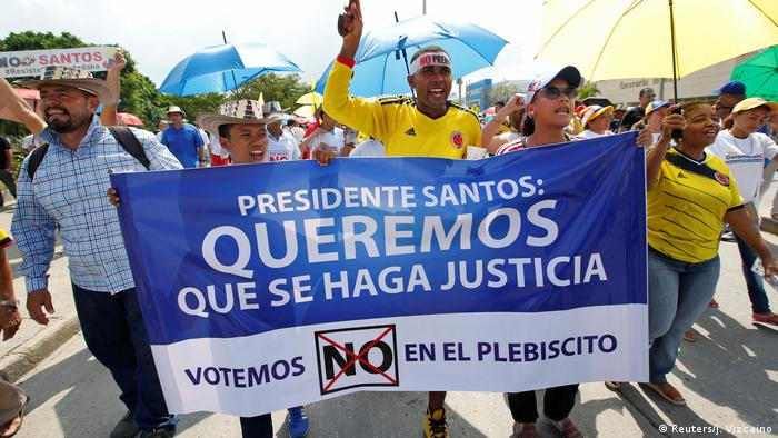 Men and women march down a street holding a sign that reads: 'President Santos, we want justice'
