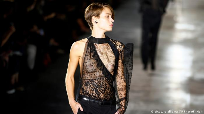 A model on a catwalk wearing a sheer black patterned top and black trousers.