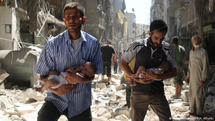 Syrien Aleppo Männer in Trümmern mit Säuglingen