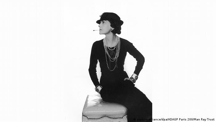 Coco Chanel posing in a black dress and hat and smoking a cigarette.
