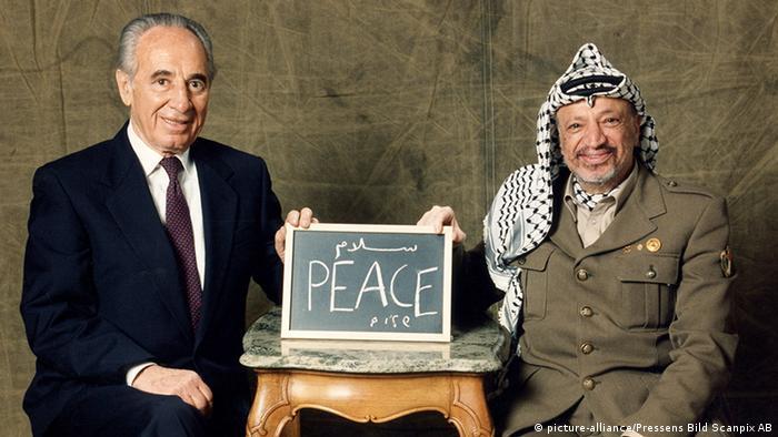 Shimon Peres e Yasser Arafat mostram um quadro com os dizeres paz