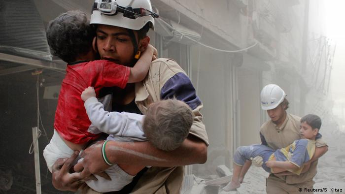 A member of the Syrian civil defense in Aleppo after an air strike.