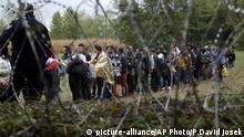 FILE - In this Saturday, Sept. 26, 2015 file photo, a group of migrants, seen through razor wire, crosses a border from Croatia near the village of Zakany, Hungary. Together, Hungary and the Czech Republic took in just around 1,000 asylum-seekers last year. Still, rallying cries against migration have dominated the debates ahead of upcoming ballots in the two Central European countries. Hungary is holding a government-sponsored referendum on Oct. 2 2016, seeking political support for the rejection of any future mandatory EU quotas to accept refugees. (AP Photo/Petr David Josek, file) |