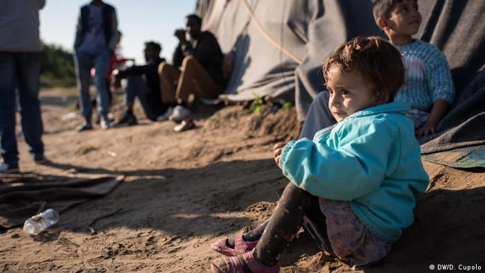 A Yazidi child sits on the floor at a refugee camp on the Hungarian border