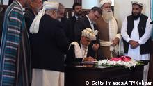 29.09.2016 *** Afghan President Ashraf Ghani (C) signs a peace deal with Afghan warlord Gulbuddin Hekmatyar, who was displayed on a video projector screen, at the Presidential Palace in Kabul on September 29, 2016. Notorious Afghan warlord Gulbuddin Hekmatyar called for peace as he appeared by video to sign a deal with President Ashraf Ghani on September 29, marking a symbolic victory in Kabul's struggle to revive talks with the Taliban. The deal paves the way for Hekmatyar, who heads the now largely dormant Hezb-i-Islami militant group but has been in hiding for years, to make a potential political comeback despite a history of war crimes. / AFP / WAKIL KOHSAR (Photo credit should read WAKIL KOHSAR/AFP/Getty Images) © Getty Images/AFP/Kohsar