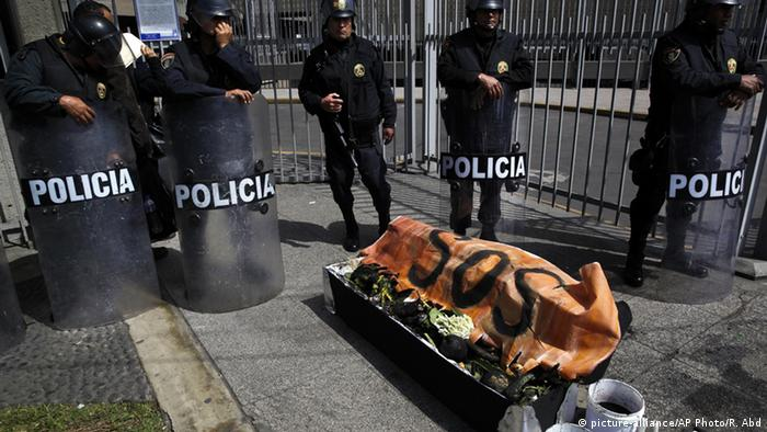 Protest in Peru with a coffin filled with black items to represent environmental contamination due to pipelines