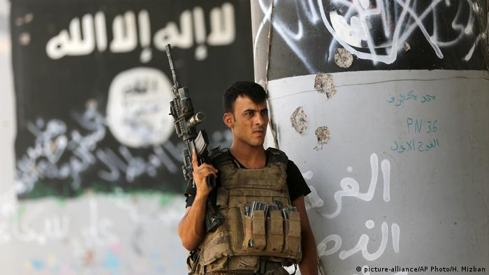 A member of Iraqi counterterrorism forces stands guard near graffiti supportive of the Islamic State after expelling the group from Fallujah