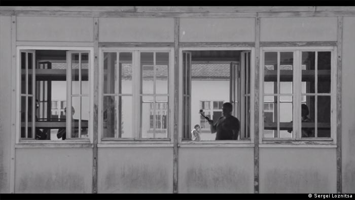 A person's shadowy profil appears in a building window in a film still from 'Austerlitz' by Sergei Loznitsa