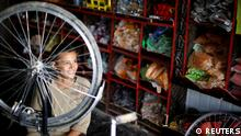 A Syrian refugee boy smiles as he work at bicycle repair shop at the main market, in the Al-Zaatri refugee camp in the Jordanian city of Mafraq