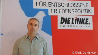 Alexander Neu stands in front of a Linke poster