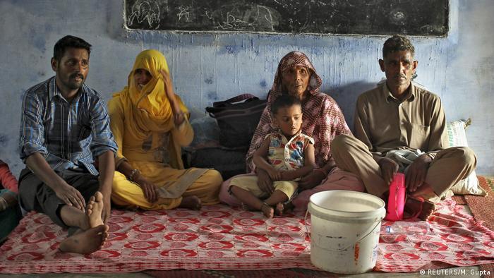 Männer und Frauen sitzen in Hilfscamps auf dem Boden, nachdem ihre Dörfer evakuiert wurden (Foto: Reuters)