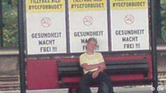 A young man sits at a bus stop, in front of posters that read Health Liberates