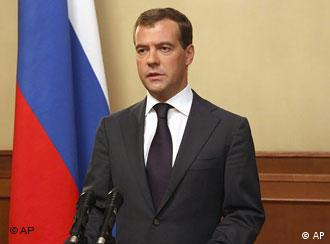 Medvedev standing in front of a Russian flag